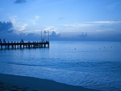 Tourists Watching Sunset from Occidental Grand Cozumel Resort Pier by Dennis Johnson