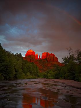 Sedona's iconic Cathedral Rock with afternoon light and rainbow reflected in Oak Creek. by Derek Von Briesen