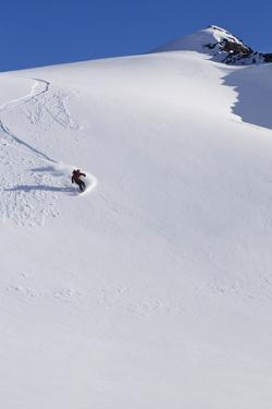 Backcountry Snowboarder Carving Turns Down a Steep Mountain Face by Design Pics Inc
