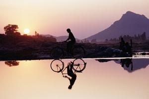 Bicyclist Crossing Shallow River at Sunset with Women in Background Doing Washing by Design Pics Inc
