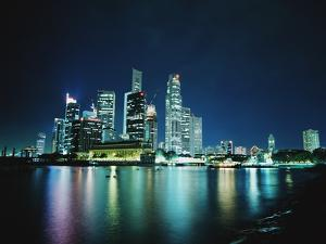 Business District Skyline at Night, with Reflections in Water by Design Pics Inc