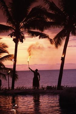Native in a Grass Skirt Holding a Flaming Torch by Coast at Sunset by Design Pics Inc