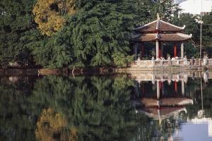 People Resting under Pagoda on Hoan Kiem Lake Shore by Design Pics Inc