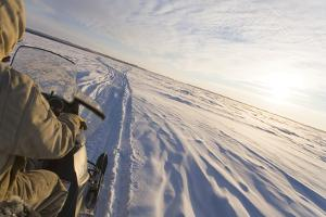 Snowmachiner Following Trail on Frozen Snow Covered Kuskokwim River Western Alaska Winter by Design Pics Inc