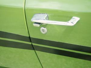 Detail of a Chrome Door Handle on a Green Car with Dark Green Stripes