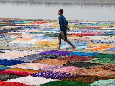 A Dhobiwala (Laundryman) Walking Among Washing on Banks of Yamuna River
