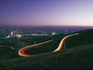 Time Exposure of Headlights Streaking Down a Highway at Twilight by Dick Durrance