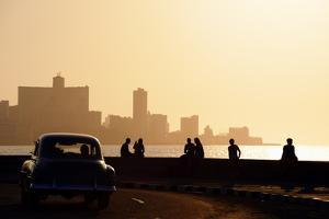 Skyline in La Habana, Cuba, at Sunset, with Vintage Cars on the Street and People Sitting on the Ma by Diego Cervo