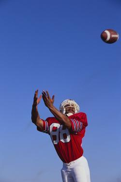 Football Player Catching a Football by DLILLC