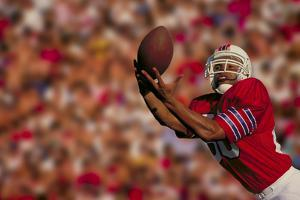 Football Player Catching Ball by DLILLC