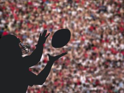 Football Player Catching Ball by DLILLC