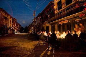 Diners Sit at a Candlelit Cafe on Bandipur's Main Street at Night by Dmitri Alexander