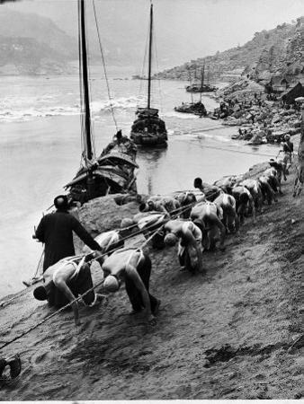 2 Rows of Chinese Trackers Plodding Along Bank of Yangtze River Towing a Junk Slowly Up River by Dmitri Kessel