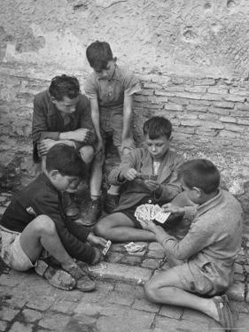 Boys Playing Cards on Steps in Town by Dmitri Kessel