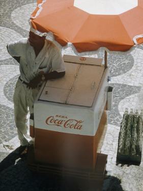 Coca-Cola Vendor Leaning on Cart with Umbrella on Mosaic Sidewalk, Copacabana Beach, Rio de Janeiro by Dmitri Kessel