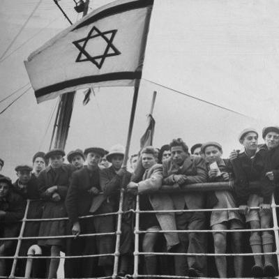 Jewish Immigrants, Arriving in Haifa Aboard Refugee Ship, Waving Future Flag of the State of Israel by Dmitri Kessel