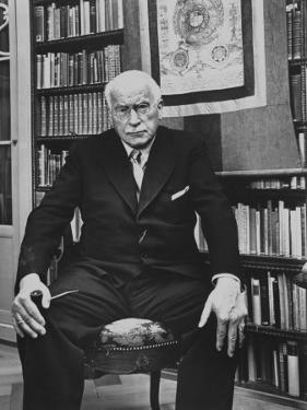 Swiss Psychiatrist Dr. Carl Jung Holding Pipe as He Sits on Chair in His Library at Home by Dmitri Kessel