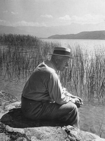 Swiss Psychiatrist Dr. Carl Jung Sitting on Stone Wall Overlooking Lake Zurich by Dmitri Kessel