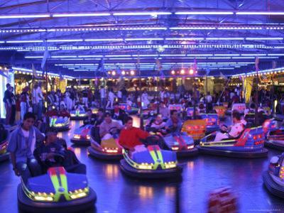 Teenagers Ride Bumper Cars under Neon Blue Lights