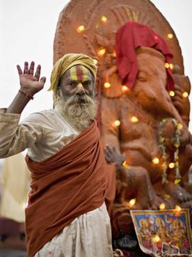 Holy Man in Front of a Ganesh Statue Draped in Fairy Lights at the Hindu Festival of Shivaratri by Don Smith