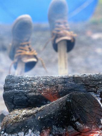 Shoes Drying on Sticks Next to Campfire