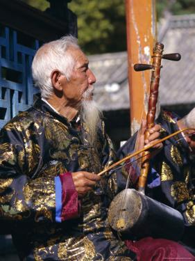 Portrait of an Elderly Musician from the Naxi Orchestra Practising by the Black Dragon Pool, China by Doug Traverso