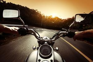 Driver Riding Motorcycle On An Asphalt Road Through Forest by Dudarev Mikhail
