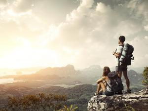 Hikers With Backpacks Enjoying Valley View From Top Of A Mountain by Dudarev Mikhail