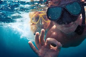 Young Couple Having Fun Underwater and Showing Ok Sign by Dudarev Mikhail