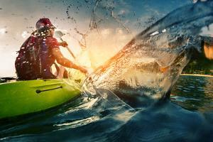 Young Lady Paddling Hard the Kayak with Lots of Splashes by Dudarev Mikhail
