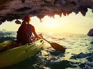 Young Lady Paddling the Kayak from Limestone Cave towards Open Sea by Dudarev Mikhail