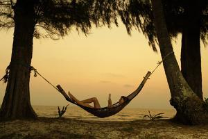 Young Lady Reading the Book in the Hammock on Tropical Beach at Sunset by Dudarev Mikhail