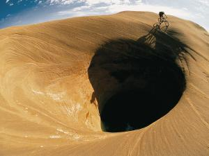 A Mountain Biker Cycles Around a Spectacular Crater in the Desert by Dugald Bremner