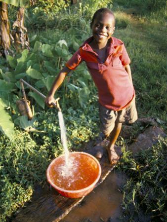 Boy at Water Tap, Chuka Village, Mount Kenya, Kenya, East Africa, Africa