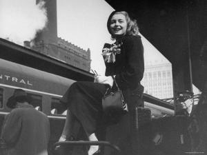 Actress Patricia Neal Sitting on Her Luggage on the Platform of a Train Station During a Stopover by Ed Clark