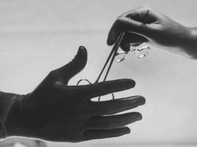 During Training of Surgeon, Often Used Clamp Is Slapped into His Hand by Ed Clark