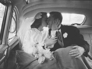 Mr. and Mrs. Thomas Beagan Jr. Kissing in Back of Car after their Wedding Ceremony by Ed Clark