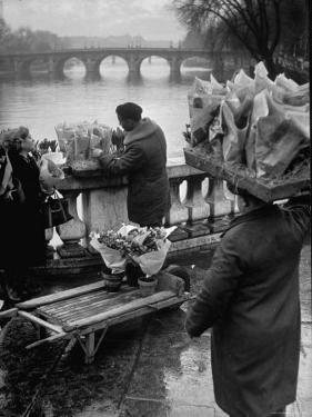 Parisian Flower Vendor at Work Stocking His Stall on the Seine with the Pont Neuf in the Background by Ed Clark