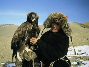 A Kazakh Eagle Hunter Poses with His Eagle on a Plain in Kazakhstan by Ed George