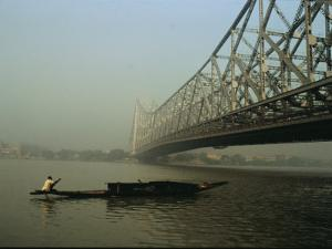 A Man Guides a Boat under a Bridge on the Hooghly River at Calcutta by Ed George