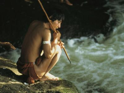 A Pinare Indian Sits by a Stream Fishing
