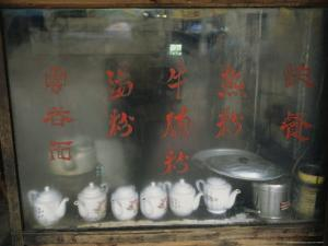 Teapots on the Sill of a Restaurant Window Covered with Steam by Ed George