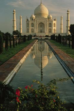 The Taj Mahal with a reflection of the tomb on  the surface of a pool. by Ed George
