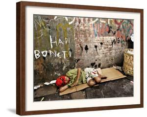 An Indonesian Boy Wearing a Spiderman Mask Sleeps on a Piece of Cardboard by Ed Wray