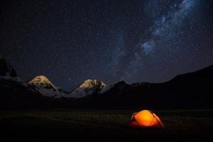 A campsite and the starry sky with snowcapped mountains in the background by Edson Vandeira