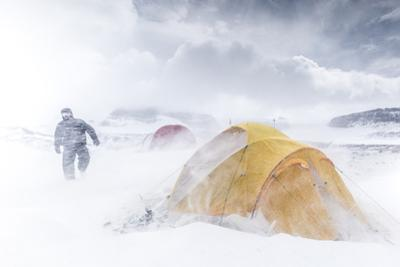 A researcher walks next to his tent during a snowstorm with strong winds in Antarctica. by Edson Vandeira
