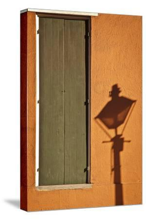 A Streetlight Casts a Shadow Near a Door on a Bright Orange Wall by Eduardo Rubiano