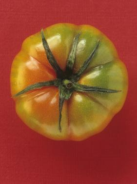 A Beefsteak Tomato Against a Red Background by Eising Studio - Food Photo and Video