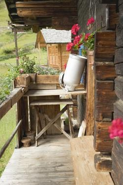 A Empty Milk Can Upside Down on Wooden Table Outside an Alpine Chalet by Eising Studio - Food Photo and Video