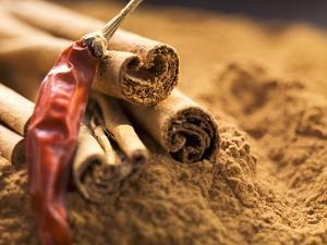 Cinnamon Sticks and Dried Chilli on Ground Cinnamon by Eising Studio - Food Photo and Video